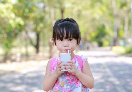 Closeup of little girl drinking milk with straw in the park. Portrait outdoor. Standard-Bild