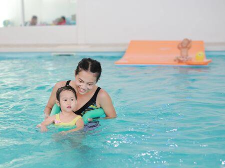 Mother teaching kid in swimming pool with foam noodle Zdjęcie Seryjne