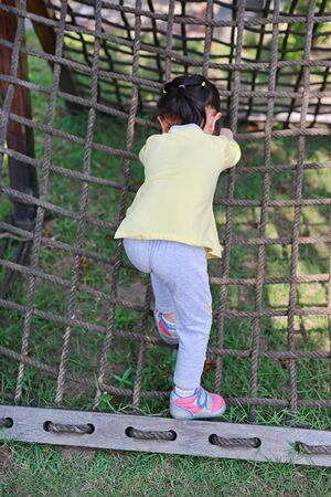 Back view of little child girl playing on climbing net.