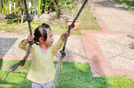 Little child girl playing on climbing rope