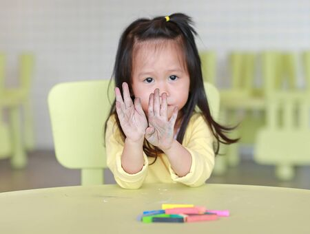 Little asian child girl with dirty hands chalk, Focus at child hands. Stock Photo