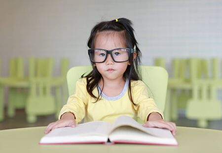 Clever little child girl wearing glasses reading a book in the kids room.