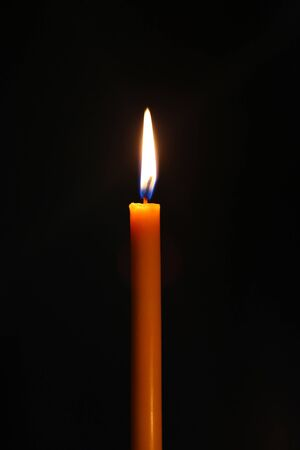 One candle burning brightly in the dark.