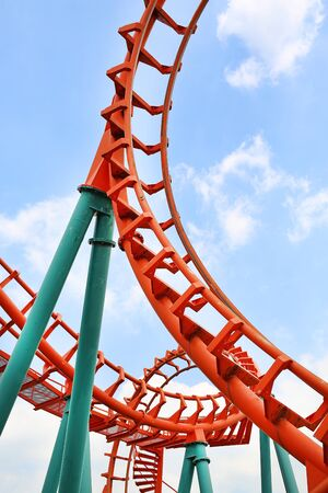 Roller coaster against cloud sky background.