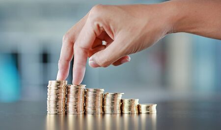 Woman finger walking up stack of coins. Saving money concept.
