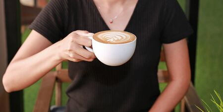 Woman drinking hot coffee in the morning, with heart shape pattern on coffee cup. Stock Photo