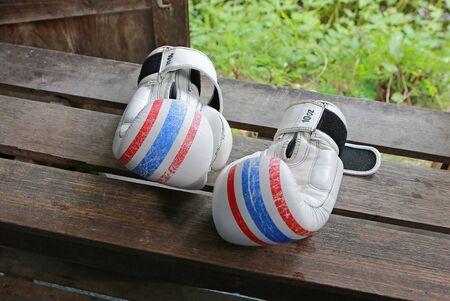 Pair of white boxing gloves paint thai flag on wooden. Stok Fotoğraf