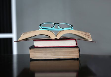 Openstack hardback books with glasses on wooden table. Education background.