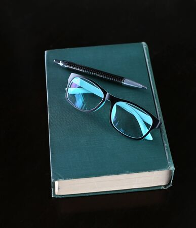Hardcover book with pen and glasses on wooden table. Education background.