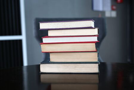 Stack of hardback books on wooden table. Education background.