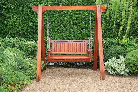 Wooden swing chair in natural green garden. Beautiful garden furniture.