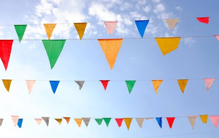 Colorful triangular Flags Hanging in the sky outdoor. Stock Photo