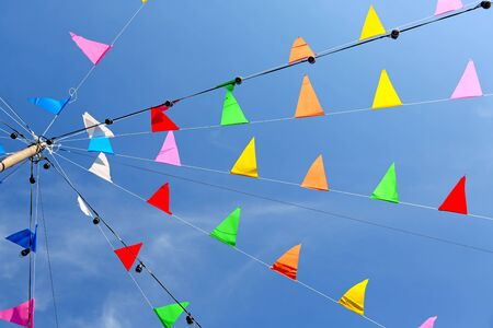 Colorful Flags in Thai temple fair against blue sky background. Stock Photo