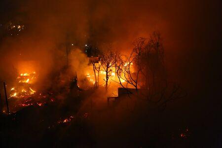 Immagine dell'albero bruciato e della casa abbandonata nella città al crepuscolo Archivio Fotografico