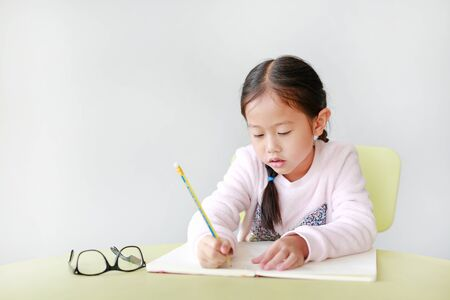 Portraits of little Asian child girl write in a book or notebook with pencil sitting on kid chair and table against white background.