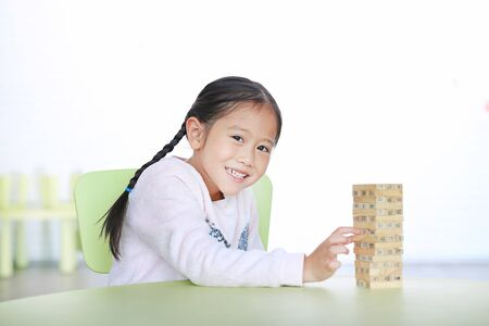 Happy little Asian child girl playing wood blocks tower game for Brain and Physical development skill in a classroom. Focus at children face. Kid imagination and learning concept. Imagens