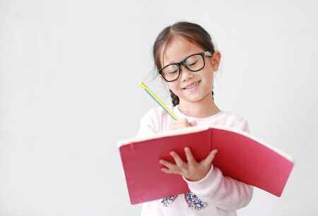 Happy little Asian child girl wearing eyeglasses and hold a book and write with pencil on white background. 写真素材
