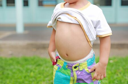 Close up little boy lifting his shirt show exposing his big tummy.