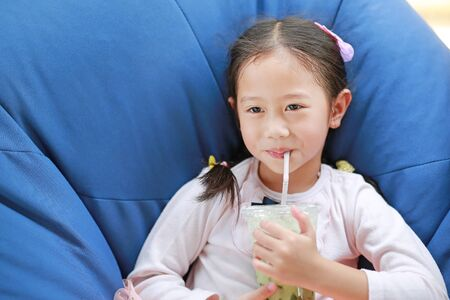Adorable little Asian child girl drinking iced Matcha Green Tea lying on sofa at cafe.