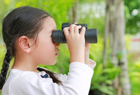 Little child girl in a field looking through binoculars in nature outdoor. Explore and adventure concept.
