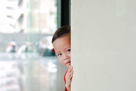 Smiling little Asian baby boy hide behind a corner room. Small children playing peekaboo game indoor. What a surprise.