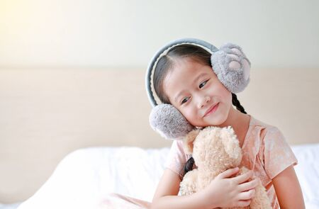 Adorable little Asian child girl wearing winter earmuffs and hugging teddy bear while sitting on the bed at home.