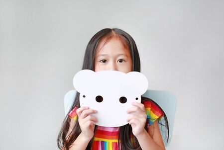 Portrait of little child girl holding blank white animal paper mask fronting her face on white background. Idea and concept for kid dressed up playing animal face. Banco de Imagens