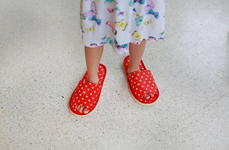 Close up child's feet wearing adult slippers at home. Archivio Fotografico