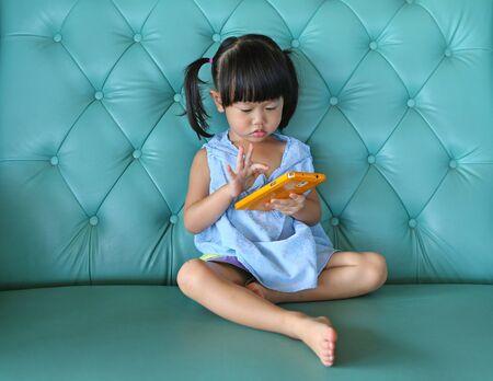child girl using smart phone on vintage sofa. asian child girl Imagens