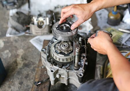 a pair of technician hand fixing the motorcycle Imagens