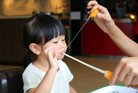 Adorable child girl eating Deep-fried Cheese Stick