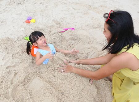 Happy loving family. Mother and her daughter child girl playing sand with animal block forming at the beach Imagens