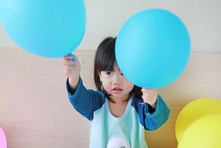 Cute little asian girl playing on bed with balloon.