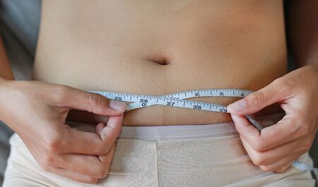 Close-up woman body fat overweight. measure tape or line tape.