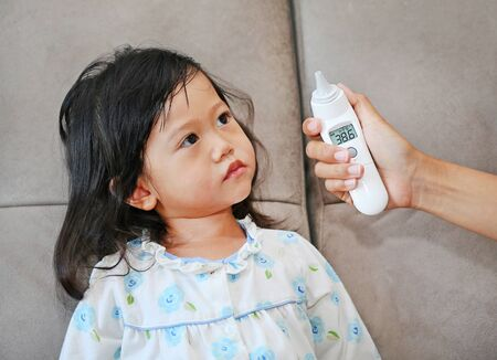 Mother takes temperature for her daughter with ear thermometer at home Stock Photo