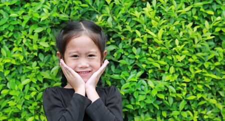 Little Asian child girl smiling and holds cheeks by hand with looking camera against leaves wall background in the garden. Foto de archivo - 133715818