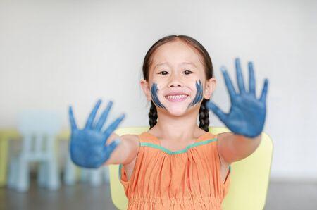 Feliz niña asiática con sus manos azules y mejillas pintadas en la habitación de los niños.