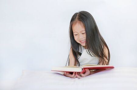 Smiling little Asian kid girl reading hardcover book lying with pillow on bed against white background.