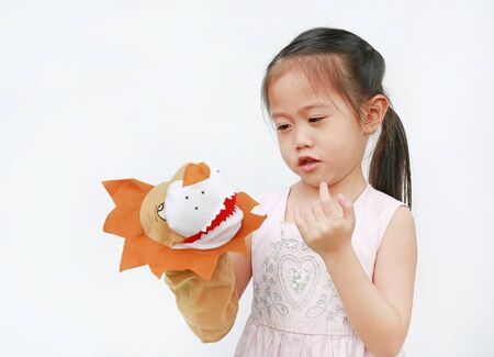 Adorable little Asian child girl hand wear and playing Lion puppets on white background. Educations concept.