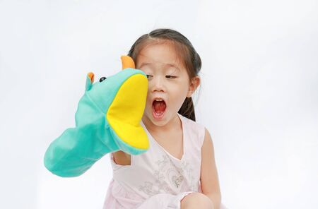 Smiling little Asian child girl hand wear and playing Rhinoceros puppets on white background. Educations concept.