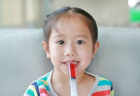 Happy little Asian child girl feeding liquid medicine with a syringe by self.