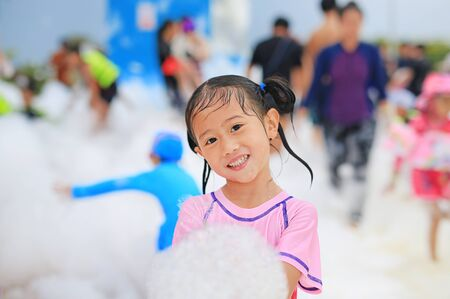 Portraits of happy little Asian child girl smiling having fun in Foam Party at the pool outdoor.