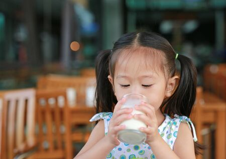 Asian little girl is drinking a milk from glass