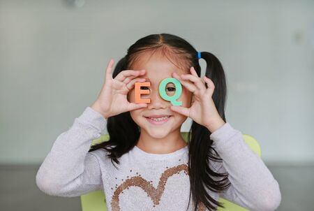 Adorable little Asian child girl holding alphabet EQ (Emotional Quotient) text on her eyes. Education and development concept. Standard-Bild
