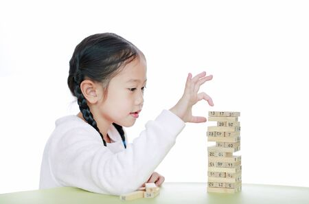 Intend little Asian child girl thinking to playing wood blocks tower game for Brain and Physical development skill in a classroom. Focus at children face. Kid learning and mental skills concept.