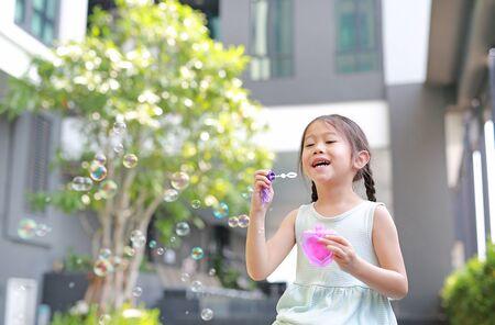 Happy little girl playing soap bubbles in garden. Stok Fotoğraf