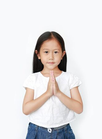 Portrait smiling beautiful little asian girl praying isolated over white background. Sawasdee is meaning hello.