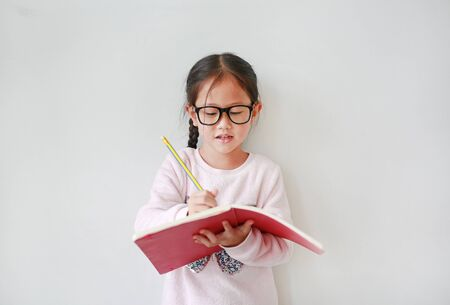 Intend little Asian girl wearing eyeglasses holding and writes in a notebook with pencil on white background.