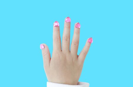 Kid nails with fashion jewels isolated on cyan background. Close up shot. 写真素材 - 133666411