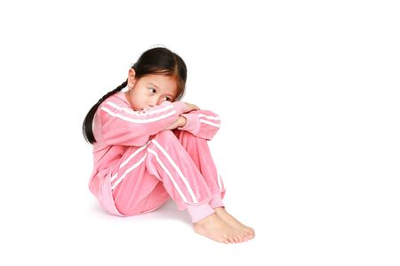 Sad little Asian child girl in pink tracksuit or sport cloth sitting and hugging knees over white background with looking out.